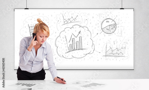 Business woman sitting at table with hand drawn graph charts