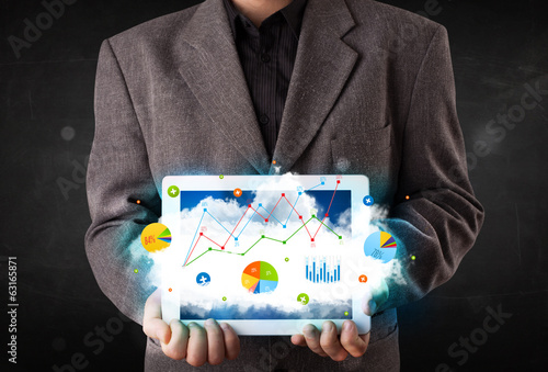 Leinwandbild Motiv Person holding a touchpad with cloud technology and charts
