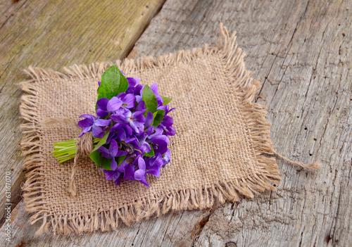 Small bouquet with meadow violets on board.