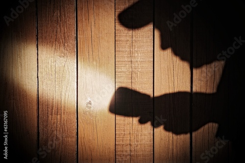 Human silhouette with flashlight in shadow on wood background, X