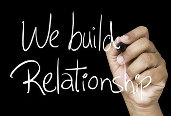 We build relationship hand writing on black marker