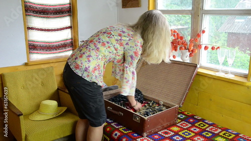 Blond woman girl unpack her clothes into retro travel suitcase