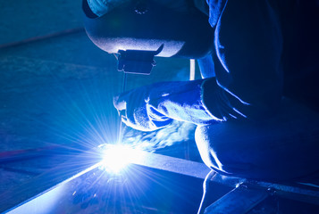 Welder working on metal with protective mask for construction