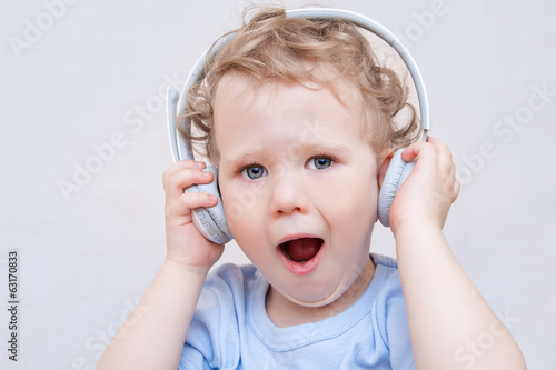Boy with white headphones on the head listening to the music