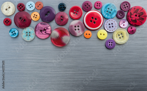 Sewing buttons on brushed metal background