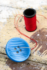 blue button with needle and thread background