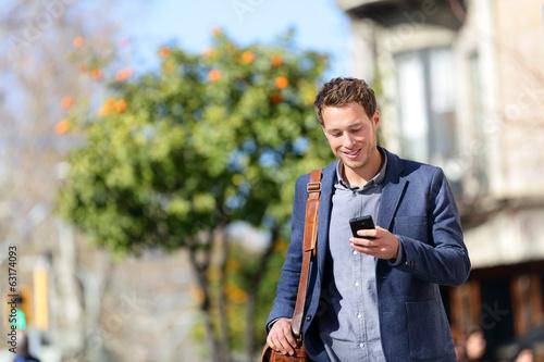 Leinwandbild Motiv Young urban professional man using smart phone