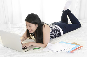 chinese student or business woman lying on bed computer working