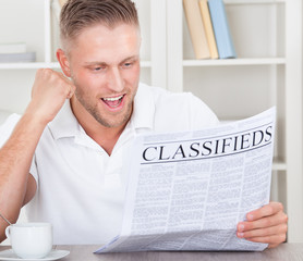 Excited man reading the classifieds cheering