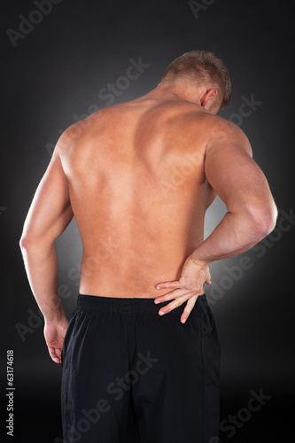 Strong muscular man with backache