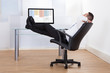 Relaxed Businessman Sitting Feet Up At Desk