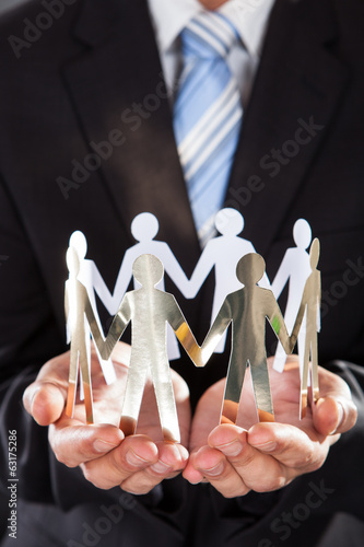 Businessman Holding Metal Team In Cupped Hands