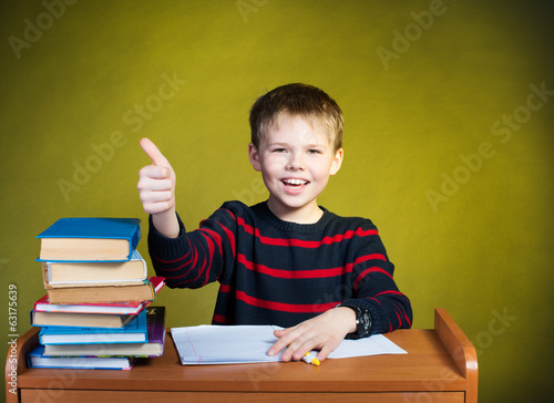 Happy boy doing homework with thumb up, books on table