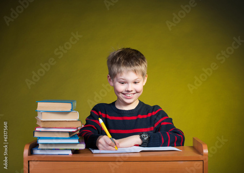 Funny boy doing homework, books on table