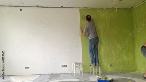 Two men painting a wall with roller. Time lapse video
