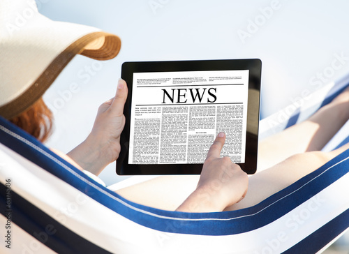 Woman Reading Newspaper On Digital Tablet In Hammock