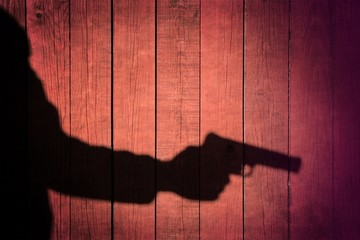 Outstretched arm with a gun. Black shadow on wooden background.