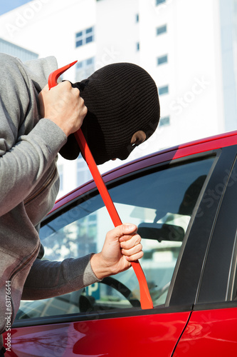 Thief In Hooded Jacket And Balaclava Opening Car's Door