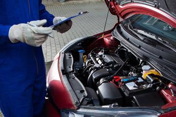 Mechanic Holding Clipboard In Front Of Open Car Engine