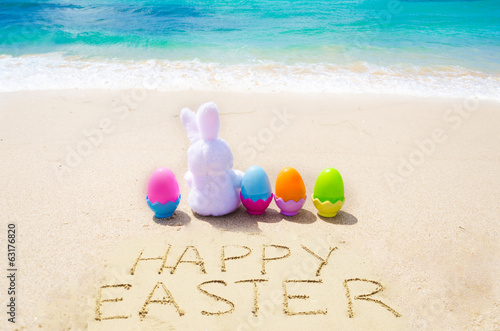 "Sign ""Happy Easter"" with bunny and color eggs on the  beach"