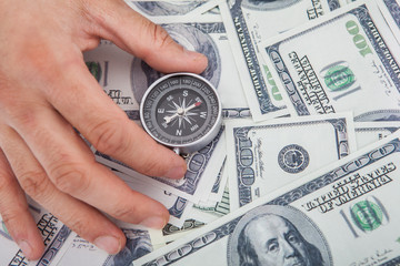 Hand Holding Compass On Us Currency