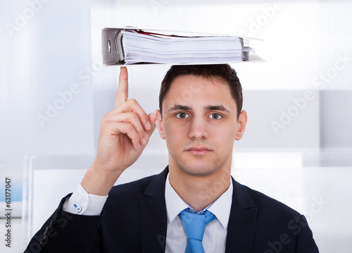 Businessman Balancing Binder On Head With Finger