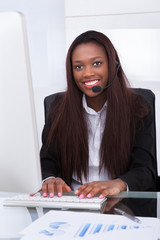 Customer service representative working at desk in office