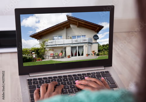 African American woman selecting new house on laptop at home