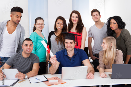 College Student Holding Degree With Classmates Looking At Him