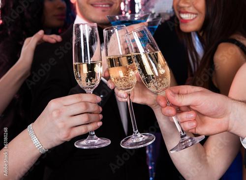 Leinwanddruck Bild Friends Toasting Champagne At Nightclub