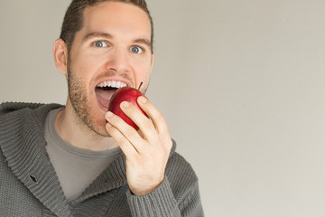 Young man eating a red apple