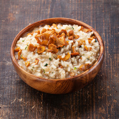 Risotto with chanterelles in wooden bowl