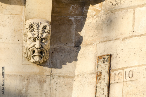 Gargoyle head and flood meter on the pont neuf