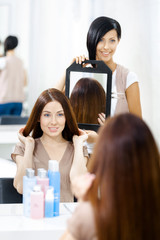 Hairdresser showing the ready haircut of the female client