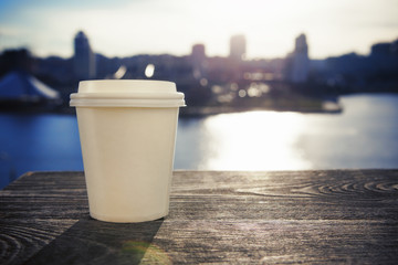 paper cup with take-out coffee on city background