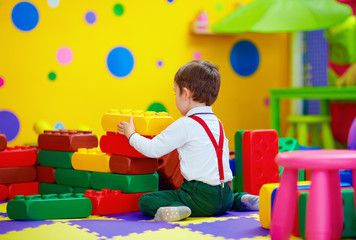 happy kid playing with toy blocks in kindergarten