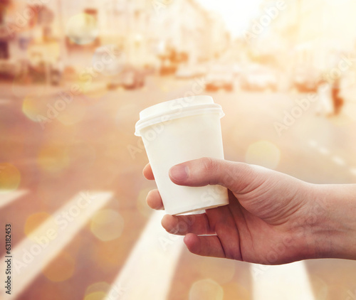 hand holding paper cup with take-out coffee at city street