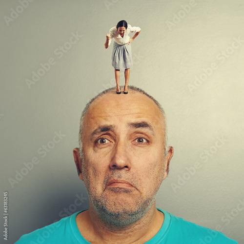 sad man with small angry businesswoman
