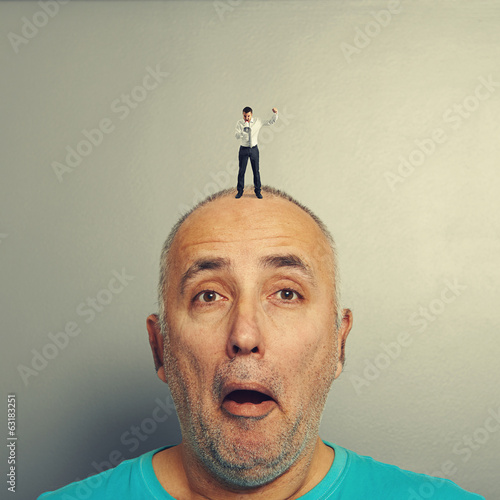 surprised man with small angry businessman