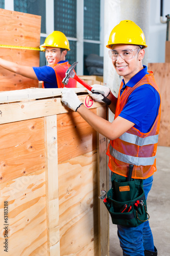 Worker close a wood box with hammer and nail