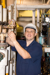 Engineer with hard hat works on boiler