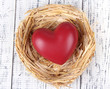 Decorative heart in nest, on wooden background