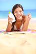 Sunscreen woman showing suntan lotion bottle