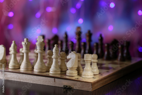 Chess pieces on board on bright background