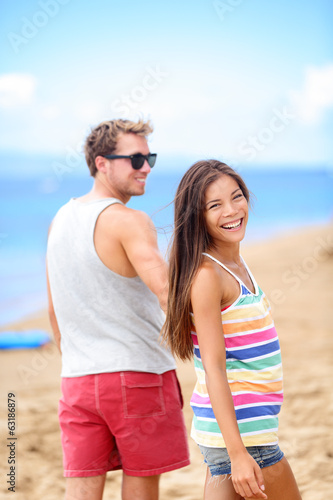 Happy romantic couple on beach holding hands