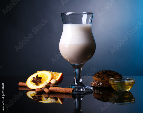 Eggnog with spices and orange on colorful background