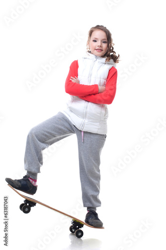 Adorable little skateboarder isolated on white