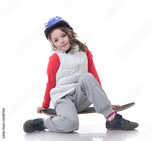 Curly little skateboarder posing at camera