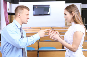 Work colleagues arguing at conference hall