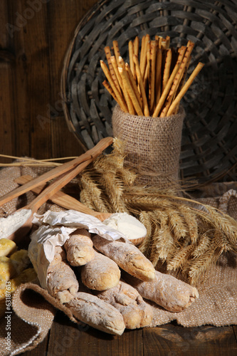 Bread sticks on sackcloth on wooden background